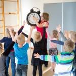 Miranda Molhoek tijdens bewegend leren, dansen met de kinderen, hier houdt Miranda een grote klok vast